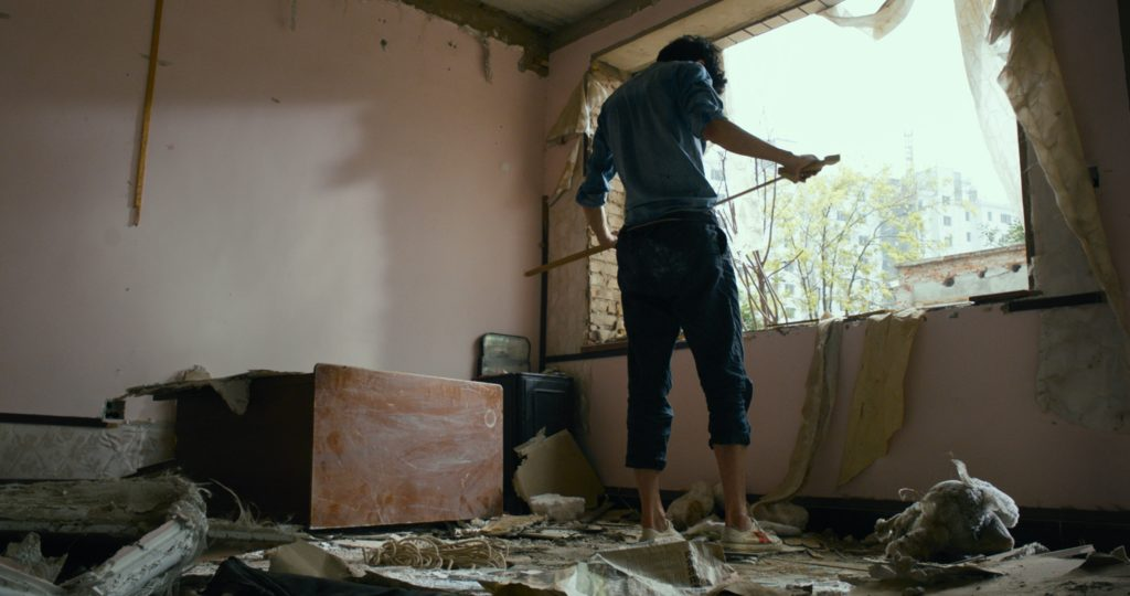 Yon Le récupère ce qu'il peut revendre dans un village en cours de destruction.